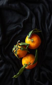 Вертикальный снимок мандаринов с зелеными листьями на черном