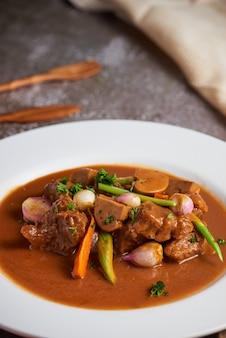 Вертикальный снимок мяса с овощами и соусом на белой тарелке
