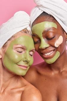 다양한 연령의 다민족 여성이 얼굴에 녹색 천연 껍질을 벗긴 마스크를 바르고 샤워를 한 후 미용 절차를 밟는 수직 사진은 실내에서 머리에 목욕 수건을 착용하고 맨 어깨에 포즈를 취합니다.