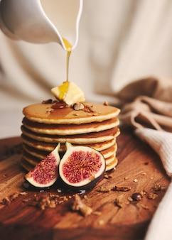 Вертикальный снимок блинов с сиропом, маслом и жареными орехами на деревянной тарелке