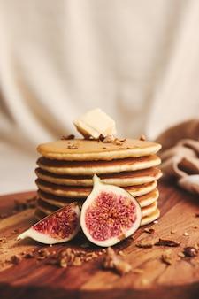 木の板にシロップ、バター、イチジク、ローストナッツとパンケーキの垂直ショット