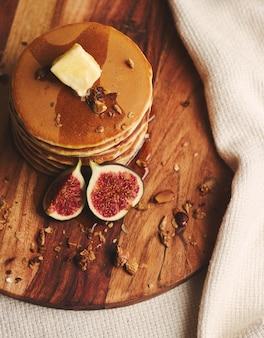 Вертикальный снимок блинов с сиропом, маслом, инжиром и жареными орехами на деревянной тарелке