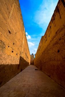 昼間の茶色の壁の真ん中にある通路の垂直方向のショット