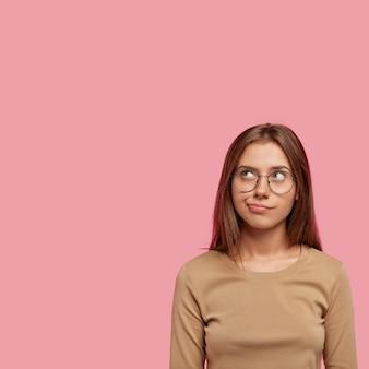 物思いにふける美しい若い女性が上向きに集中し、疑わしく思慮深く見え、カジュアルな服を着て、丸い眼鏡をかけ、ピンクの壁に隔離された垂直ショット。