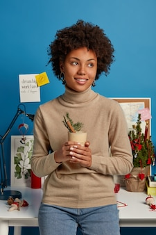 자연 아프로 머리와 잠겨있는 쾌활한 여자의 세로 샷, 에그 노그 칵테일을 마시고, 크리스마스를 축하하는 방법을 계획하고, 파란색 벽에 포즈를 취합니다. 코 워킹 스페이스에서. 휴일 전통