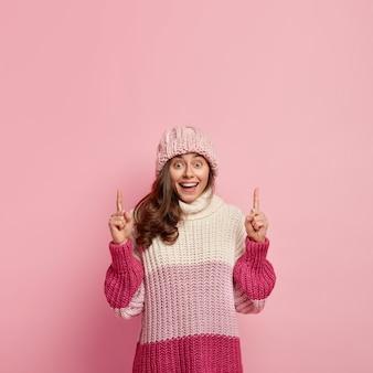진지한 미소를 지닌 유쾌하고 긍정적 인 여성의 세로 샷, 위의 포인트는 환상적인 물체를 보여줍니다. 높은 정신으로 관심을 끌고 분홍색 벽 위에 격리됩니다. 겨울