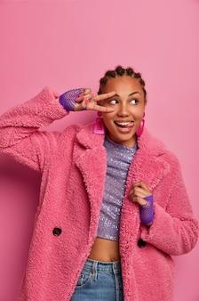 유쾌한 젊은 여성의 세로 샷은 평화 제스처를 만들고 혀를 내밀고 옆으로 보이며 긍정적 인 분위기를 가져오고 훌륭한 하루를 즐기고 분홍색 코트를 입고 콘로 우 헤어 스타일을 가지고 있습니다.