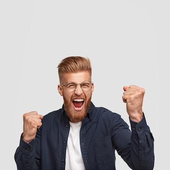 ポジティブな楽観的な生姜の男性の垂直ショットは彼の成功を祝い、拳を食いしばり、幸せで悲鳴を上げる