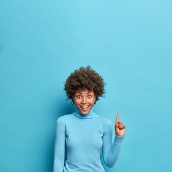 Вертикальный снимок позитивной молодой афроамериканки, демонстрирующий рекламу выше, предлагает проверить ее