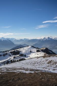 青い空の下でスイスのリギ山脈の垂直ショット