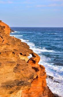 카나리아 제도의 햇빛 아래 바다로 둘러싸인 바위의 세로 샷