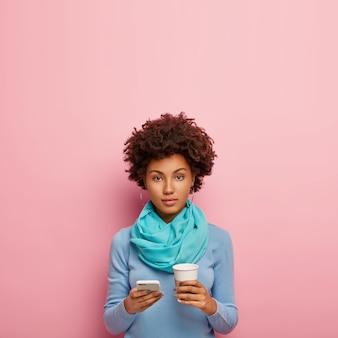深刻なアフロアメリカ人女性がテイクアウトコーヒーを飲むの垂直ショット