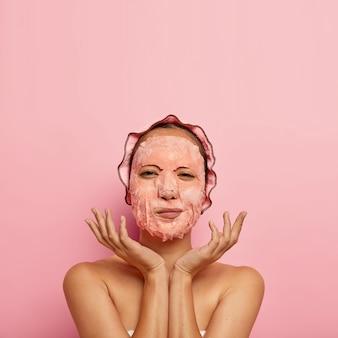얼굴 시트 마스크가있는 심각한 여성 모델의 세로 샷, 얼굴 근처에 손바닥을 퍼 뜨리고, 저녁에 집에서 뷰티 루틴을 가지고, 목욕 모자를 쓰고, 알몸으로, 분홍색 벽에 고립 된, 위의 빈 공간