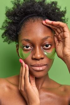 자연스러운 곱슬머리를 한 진지한 젊은 여성의 수직 샷은 눈 아래에 하이드로겔 패치를 적용하여 미세한 선을 줄이고 붓기는 선명한 녹색 벽에 셔츠를 입지 않은 채로 서 있습니다