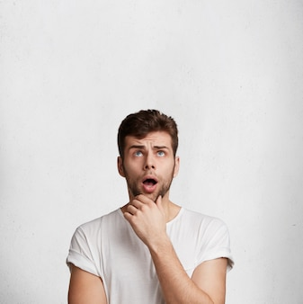 Вертикальный снимок потрясенного бородатого мужчины с широко открытым ртом, недоуменно смотрит вверх, замечает что-то неожиданное, позирует на фоне белой бетонной стены
