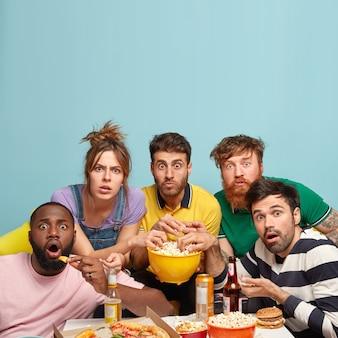 Вертикальный снимок потрясенных товарищей или товарищей из смешанной расы, смотрите фильм ужасов с попкорном, испуганные выражения лица, едят чипсы и пиццу, изолированные на синей стене со свободным пространством наверху