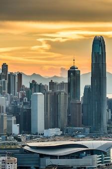 日没時のオレンジ色の空の下で香港の高層ビルの垂直ショット