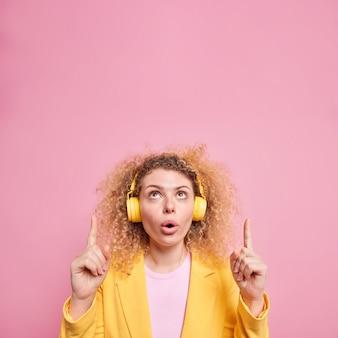 Вертикальный снимок безмолвной кудрявой женщины с удивленным выражением лица указывает вверх демонстрирует неожиданное предложение, накладывает беспроводные наушники на уши, наслаждается любимым плейлистом.