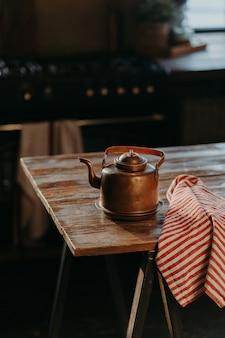 아늑한 방에 있는 나무 테이블에 있는 강철 주전자의 수직 샷. 차를 만드는 오래된 고대 알루미늄 찻주전자. 빈티지 가정용품.