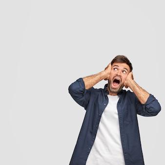 愚かな白人の若い男の垂直ショットは、耳を覆い、口を大きく開き、信じられないほど上向きに何かを見る