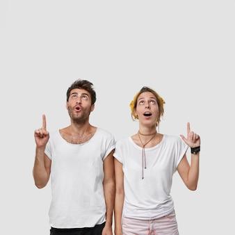 멍청한 암컷과 수컷의 세로 샷은 두 검지 손가락을 위로 향하고 충격적인 것을 나타내며 턱을 내리고 천장에 집중합니다.