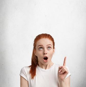 Вертикальный снимок удивленной красивой эмоциональной женщины с пучком рыжих волос, указывает вверх на пустом пространстве для копии