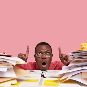 Вертикальный снимок удивленного темнокожего мужчины, широко открывающего рот, указывает указательными пальцами в потолок, в очках, у него много бумажной работы
