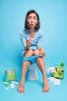 놀란 검은 머리 아시아 여성의 세로 사진은 긍정적인 임신 테스트기를 보유하고 있으며 자신이 파란색 벽에 대고 변기에서 임신한 포즈를 취하고 있음을 발견했습니다