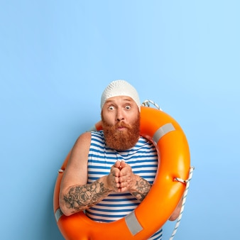 두꺼운 수염을 가진 놀란 redhaired 남자의 세로 샷, 손바닥을 함께 누르고, 다이빙 준비, 보호 고무 수영 모자, 선원 조끼 착용, 눈이 튀어 나옴