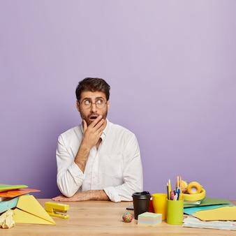 놀란 형태가 이루어지지 않은 남자 관리자의 세로 샷은 공포로 옆으로 집중된 입을 덮고 투명한 안경과 흰색 우아한 셔츠를 입고 커피, 헤드폰, 종이 비행기로 나무 책상에 앉아 있습니다.