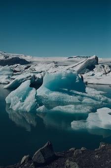 Вертикальный снимок красивых айсбергов на воде, снятых в исландии.