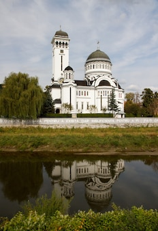 Вертикальный снимок собора святой троицы, отражающегося в озере в сигишоара, румыния