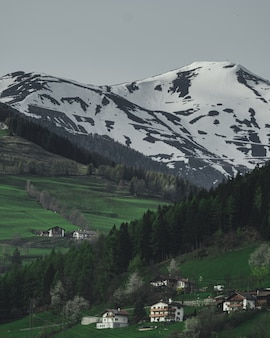 Вертикальный снимок домов на холме с красивой заснеженной горы