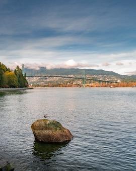 라이온스 게이트 브릿지를 볼 수있는 밴쿠버의 스탠리 공원에있는 호수의 세로 샷