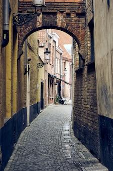 오래된 벽돌 벽이 있는 벨기에 브뤼헤의 좁은 거리의 수직 샷