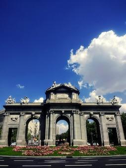 青空の下でマドリードの新古典主義記念碑プエルタデアルカラの垂直ショット