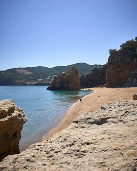 스페인의 playa illa roja 공공 해변에서 바다의 해안에있는 바위의 세로 샷