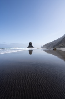 透明な水の自然な痕跡と海の岩の多い海岸の垂直ショット