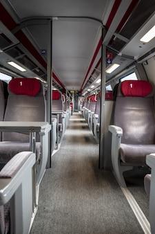 Вертикальный снимок рядов красных и серых сидений внутри пустого поезда