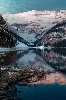 カナダのレイクルイーズに反映される雪山の垂直ショット