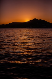 Вертикальная съемка заходящего солнца за горой в naxos, греции