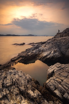 曇った空に沈む夕日の水と崖の垂直ショット