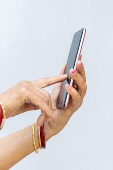 現代のスマートフォンを使用して女性のしわのある手の垂直ショット