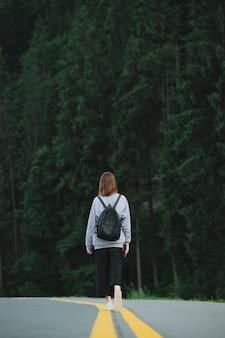 森林地帯の高速道路の中央にバックパックを持った観光客の垂直ショット