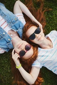 생강 머리와 주근깨가있는 두 명의 아름다운 자매의 세로 샷, 잔디에 누워 편안한 표정으로 웃고, 얼굴을 만지고, 서로에 대한 관심을 표현합니다.