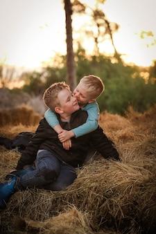 山の上に座って、お互いにキスしている2人の金髪の兄弟の垂直ショット
