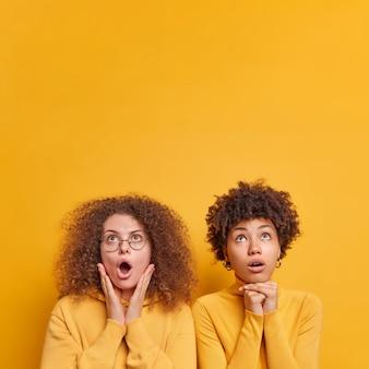 위의 충격으로 응시하는 두 명의 다양한 여성의 세로 샷은 승진을 위해 노란색 벽 복사 공간 위에 자연스럽게 격리 된 옷을 입고 서로 밀접하게 입을 열어 유지합니다.