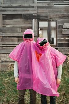 Вертикальный снимок двух человек в шлемах виртуальной реальности, одетых в розовый пластиковый плащ.