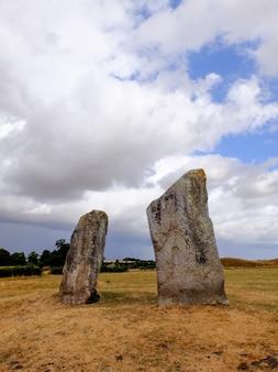 曇り空の下でフィールドの真ん中に立っている2つの岩の垂直方向のショット