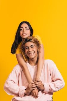 Вертикальный снимок двух улыбающихся кавказских моделей, белокурого мужчины и женщины с черными волосами, позирующих перед желтой стеной